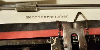 A classic typewriter, with a close-up on the phrase '@chrisbrosnahan' typed on paper