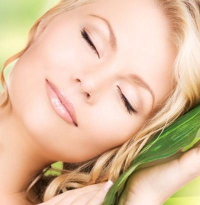 Woman with healthy young skin resting head on Aloe Vera Leaf