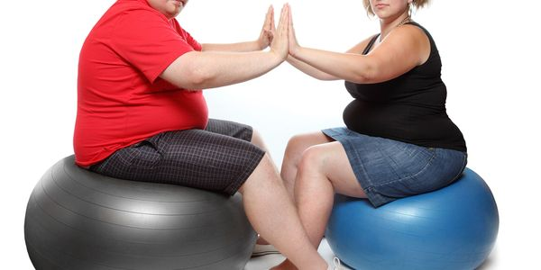 An overweight couple, sitting, facing each other on yoga balls, palms together.
