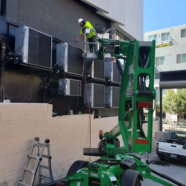 Air conditioning condenser scheduled yearly maintenance. using a man lift.