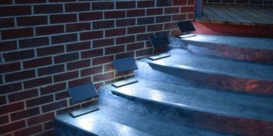 A night photo of four Step Edge Lanterns located on a patio stairway.