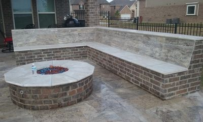 A Beautiful custom designed Seat and Fire Pit build out of Block, brick and Slade Stones.