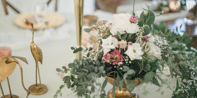 table centerpiece with brass accents.  White, purples and eucalyptus greens