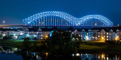 M shaped lit river bridge at night with water and apartments