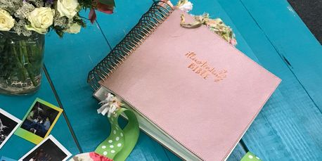 The rose gold DaySpring Illustrating Bible on a turquoise table with flowers and instant photos.