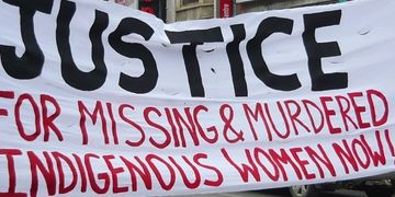 White banner with the words Justice For Missing and Murdered Indigenous Women Now