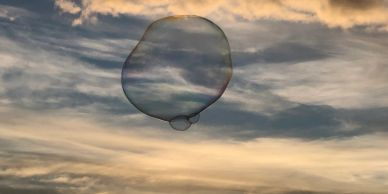 A large bubble floats in the sky. Behind it, the clouds appear as white bands across a grey blue eve