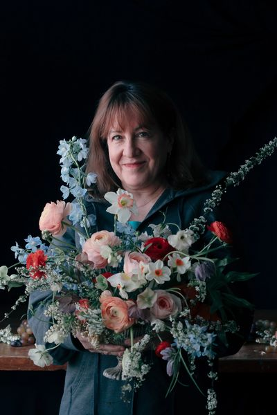 Floral Designer holding lush Dutch master inspired flower arrangement roses, tulips, narcissus