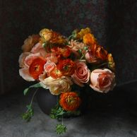 orange and peach, roses and ranunculus in a low centerpiece with greenery