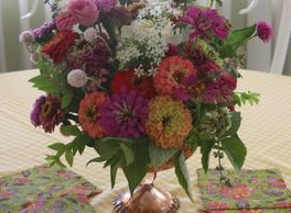 Arizona grown zinnias, gomphrena, mint, chive flowers in a colorful lush dinner party centerpiece