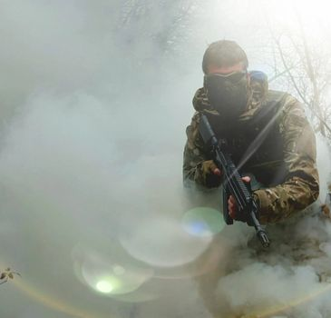 Airsofter with a rifle & smoke