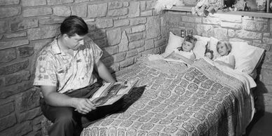 Don Lovness reading a bedtime story to his daughters in their Frank Lloyd Wright home, 1957