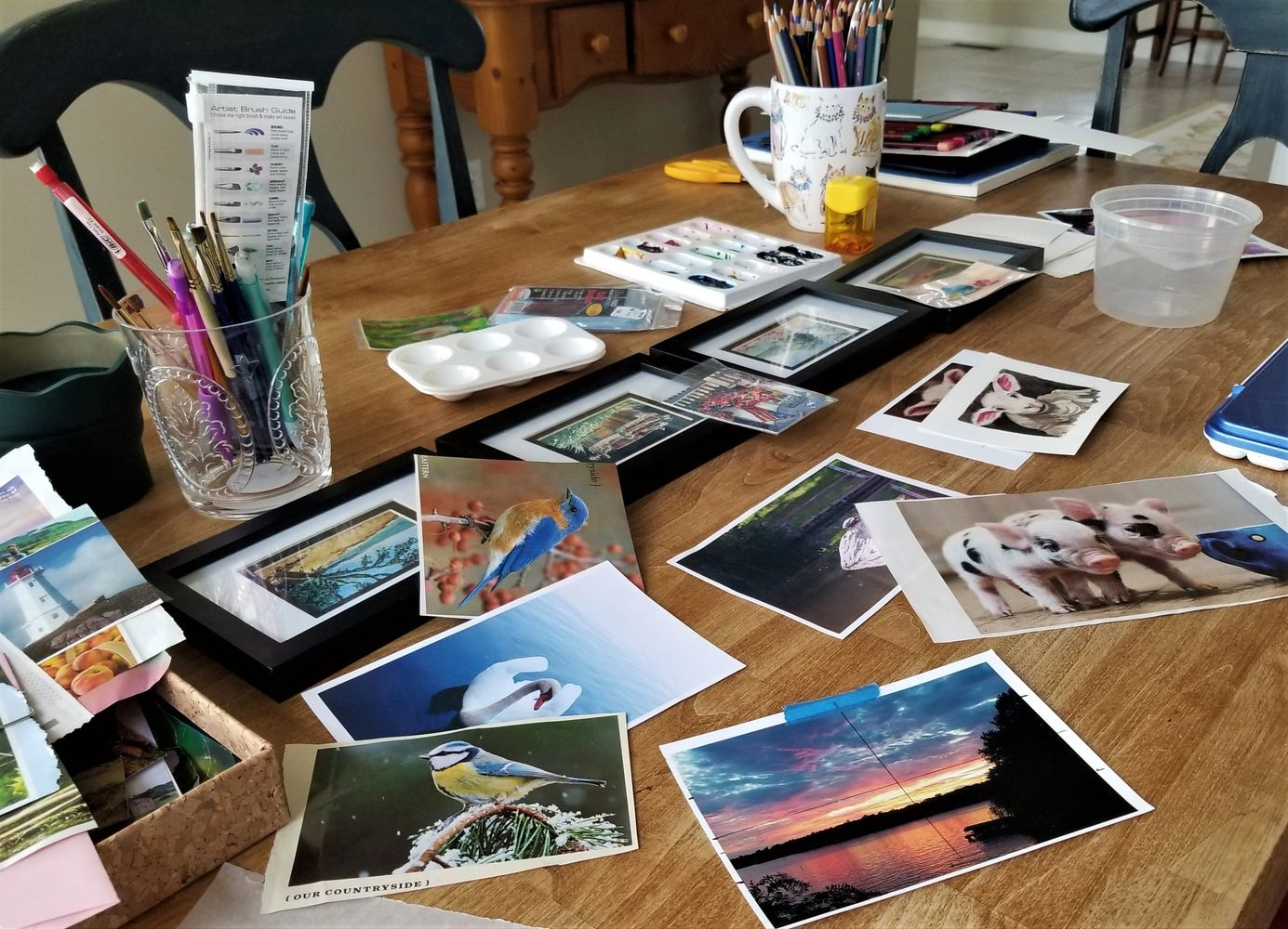 A kitchen table filled with inspiration photographs, painted pictures, pencils, brushes and paint