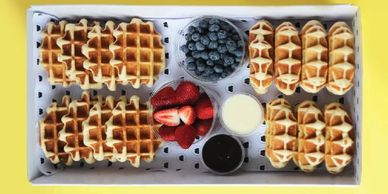 box of large waffles with chocolate strawberries and blueberries ready for delivery