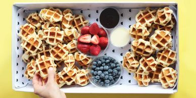 box of waffles with chocolate blueberries strawberries and mini waffles