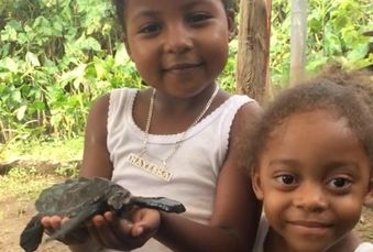 Kids on Little Corn Island with a turtle.