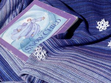 "A blue and white pinstriped piece of fabric with the book ""The Snow Child"" and tatted snowflakes."