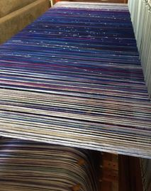 Looking at the back of a loom at the warp in white, blue, purple, and sparkle threads