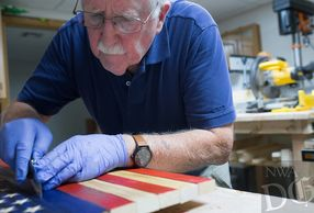 Don Lowe removing excessive glue from a rustic wooden flag with carved stars and emblems.