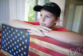 A rustic wooden American flag with carved stars.  Photo is my 11 year old grandson, Jeremiah.