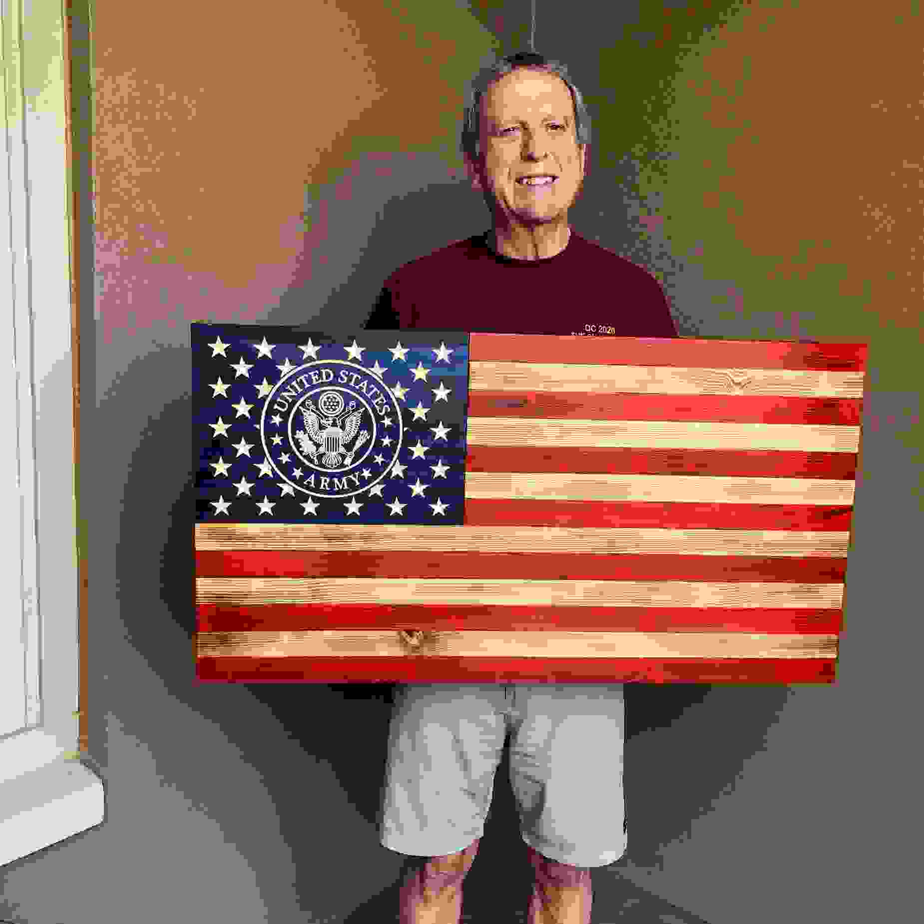 Proud vet holding his Army his rustic wooden flag.