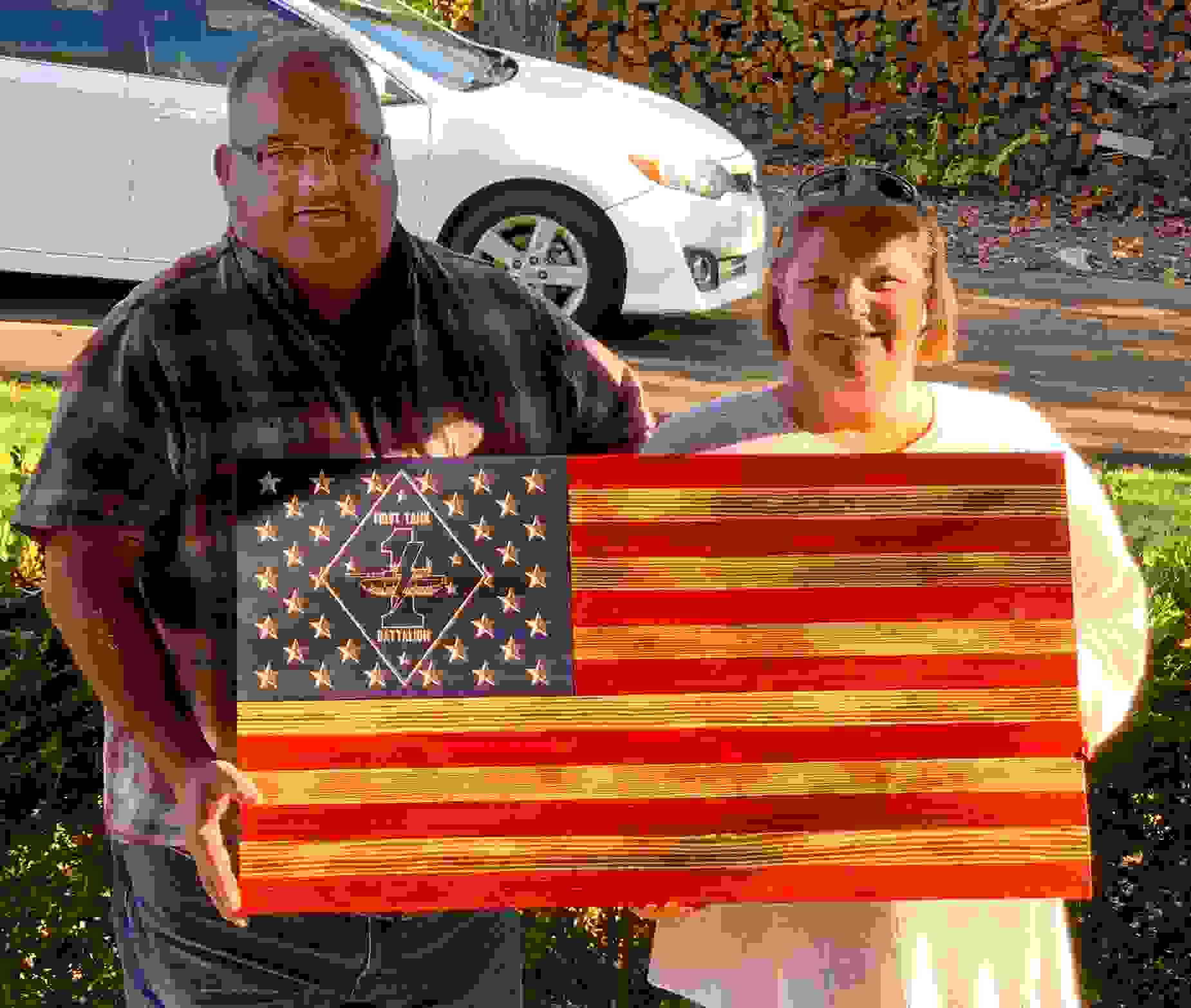 Marine Corps First Tank Battalion flag held by proud parents.
