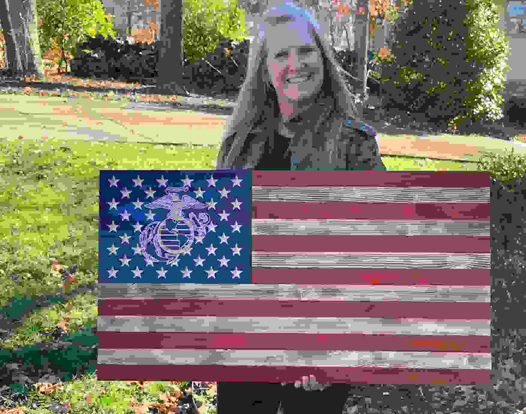 Happy customer holding a  Marine Corps flag with the EAG carved into the wood.
