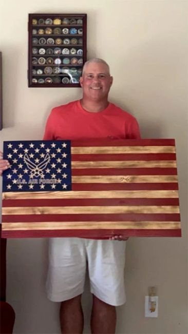 Rustic wooden Air Force flag held by a retired Veteran.