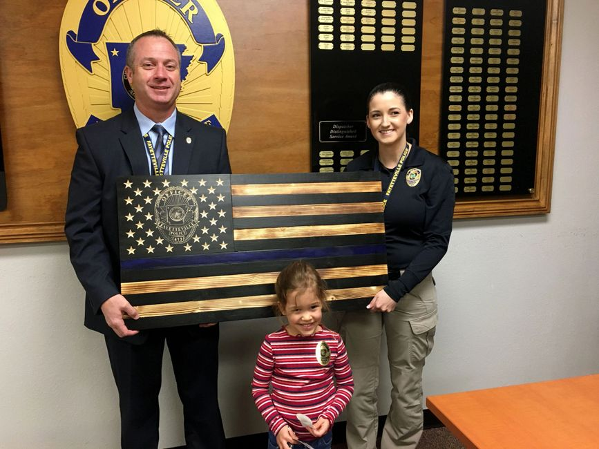 Custom Wooden Fayetteville Police flag with officer's badge carved into the wood.