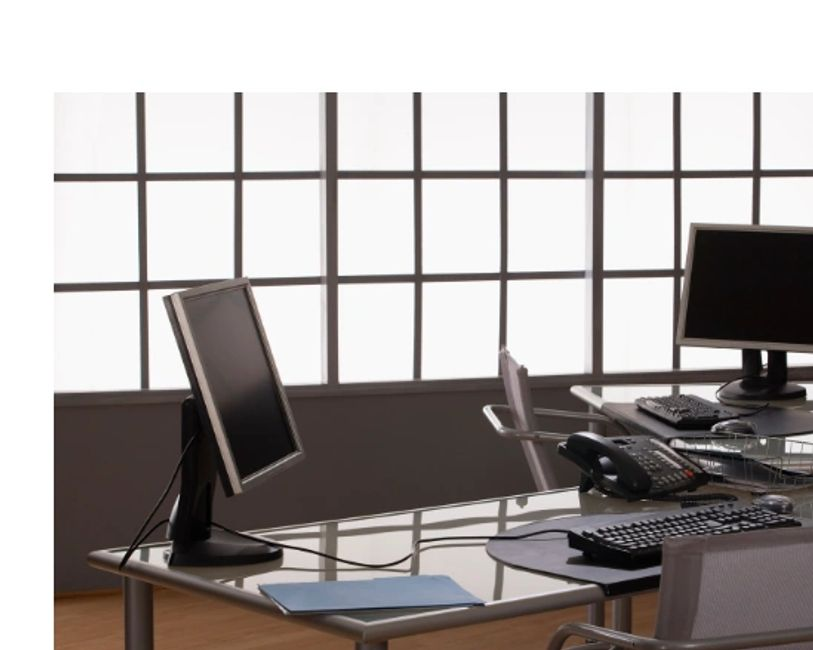 Computer workstations with chairs and telephones.