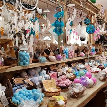 Shelves covered in bath bombs with dream catchers hanging above