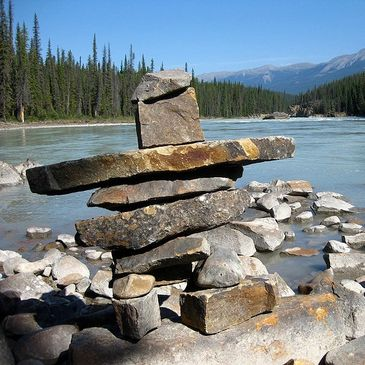 Inukshuk pointing the way, landmark for navigation, guide watches over traveler, stands out on path