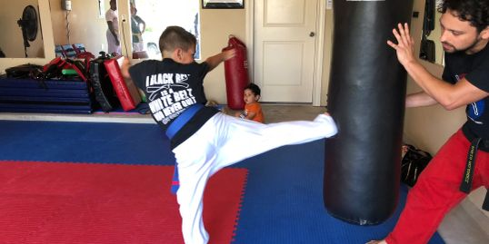 Coach Mario encouraging a young student on his step behind side kick technique.