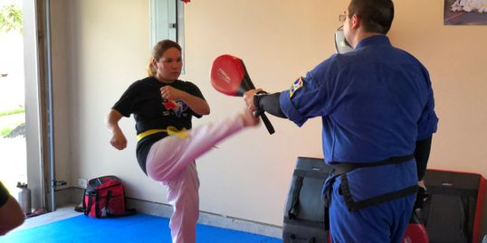 Master Blackbourn holding for one of our adult students in Pearland as she executes a Crescent Kick.