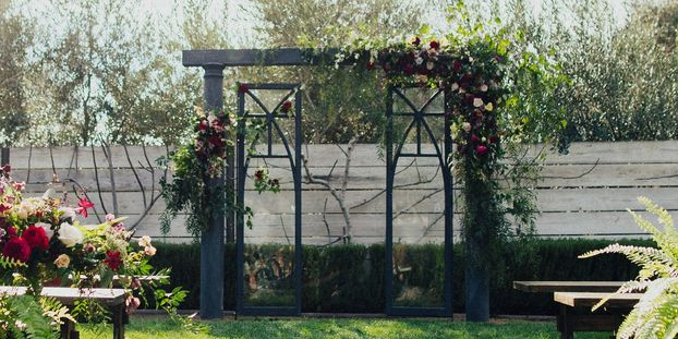 Lush Ceremony Arch adorned with merlot burgundy florals. Organic free flowing greenery with blooms.