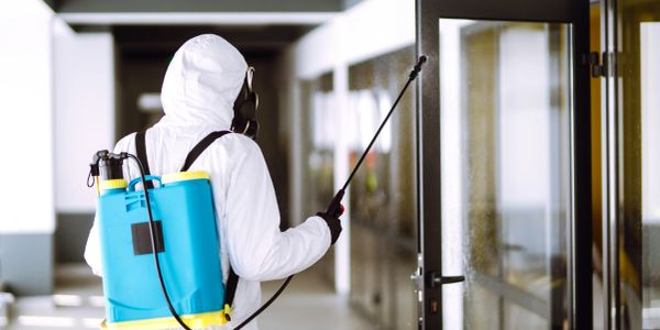 cleaner wearing PPE disinfecting business with COVID-19 coronavirus spray mist fogger service