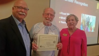 Chuck Burkitt displays an award certificate received from Kent Ellsworth and Mary Jane Thompson.