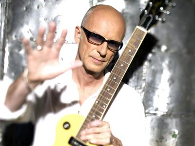 This is a photo of rock singer and songwriter Kim Mitchell.  He has one hand open towards the camera that features a wedding ring.  Kim is wearing shades and holding a Gibson-like electric guitar in his alternate hand.