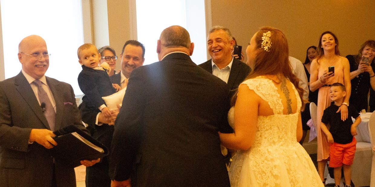 Wedding Officiant Gil Sanchez with wedding party and guests laughing. Not Boring Wedding.