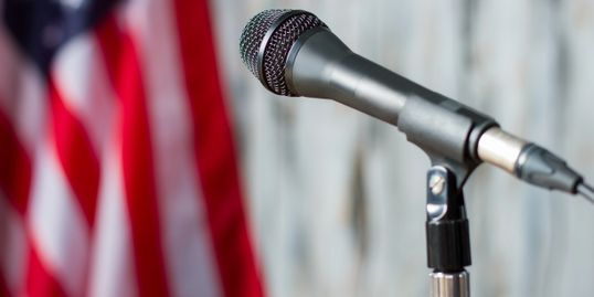 Speak Out - microphone with American flag in background.