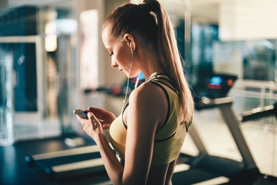 A female in gym is talking with online fitness trainer on mobile phone.