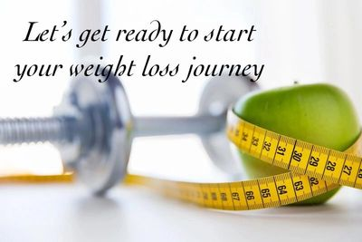 A dumbbell, apple and inch tape is placed on table to represent weight loss program.