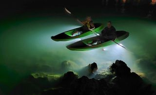 Light up the seafloor with our LED underwater lights! 2 kayakers side by side in dark with clear lit waters below. LED Illuminated kayaks www.glassbottomtours.com