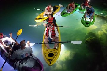 Large group of kayakers in 5 kayaks with LED lighted kayaks at night www.glassbottomtours.com