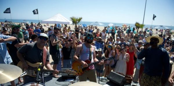 Cali Conscious performing in front of a large crowd at a beach