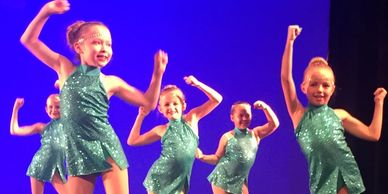 Dancers dancing on stage in teal dress