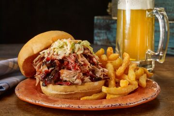Pulled pork sandwich comes with smoked shredded pork on a bun and one side