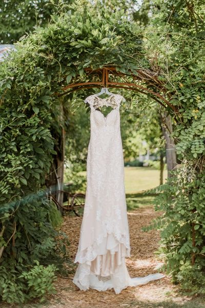 Wedding dress hanging from green arbor