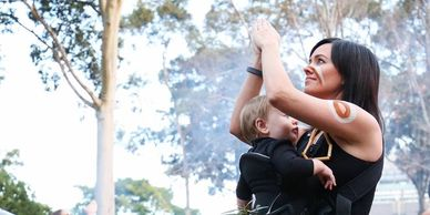Sam dancing with baby Azalea at the Stolen Generation Marker launch, 2018.