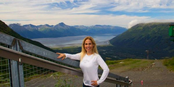 Woman standing at the peak of Mt. Alyeska in the summer overlooking the inlet